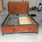 "Custom made bed. Our customer wanted the ""raw steel"" look. The bottom of the bed is fully enclosed and provided one cubic meter of storage space. The wooden boards are attached to the frame with special magnets and can easily be removed and replaced."