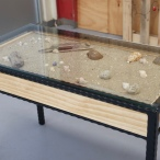 Custom made 'beach scene' table. The glass top can be removed to add new shells or to change the scenery to suit your liking